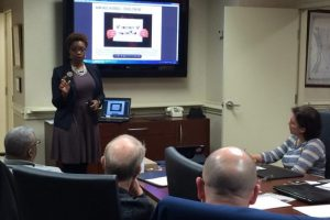 Photo of Ebony in a conference room setting talking to business owners